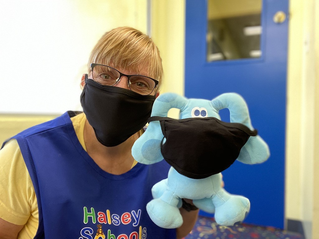 Ms Jenni wears a mask to protect other