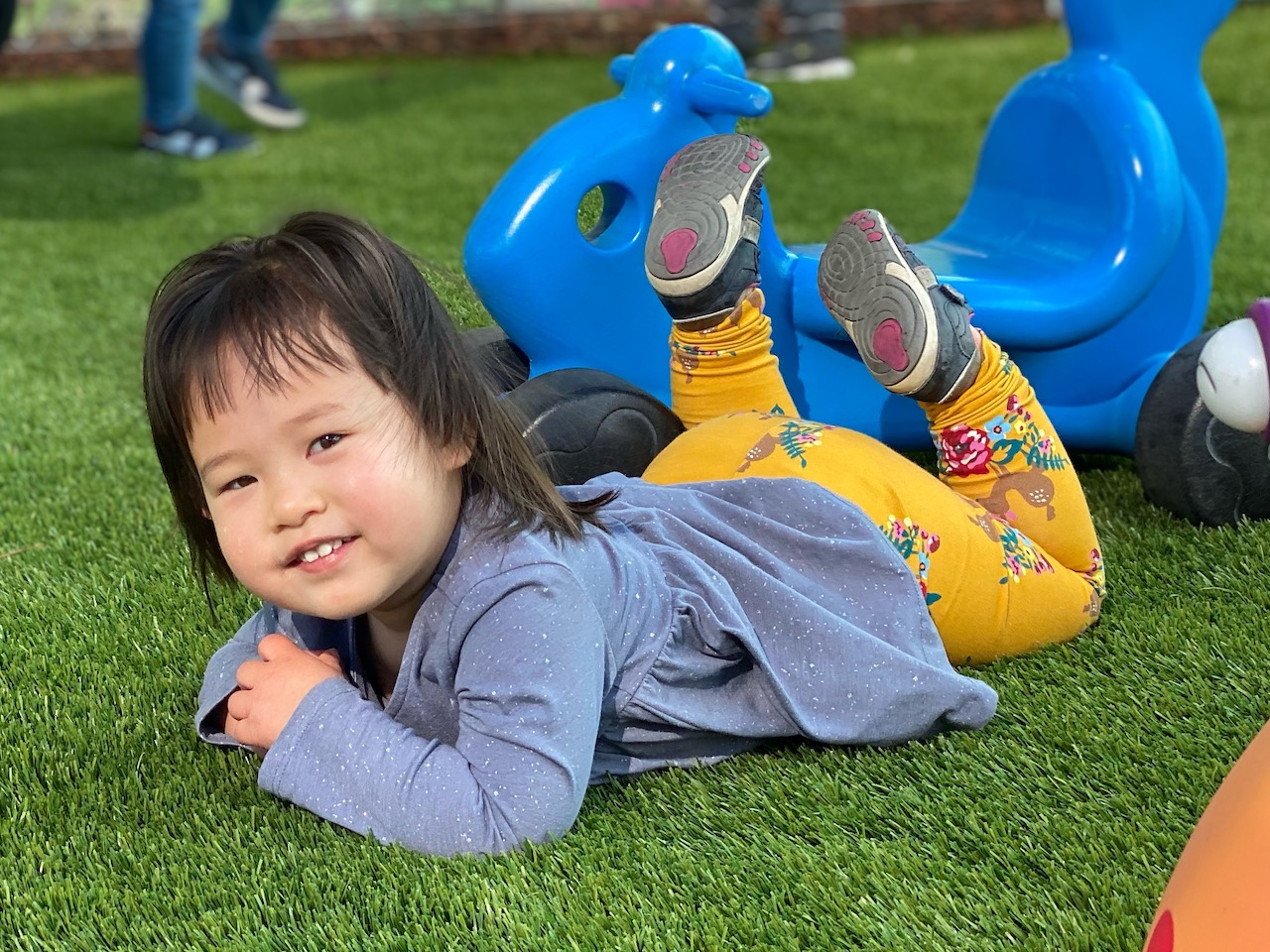 Happy Infant having fun rolling around soft turf