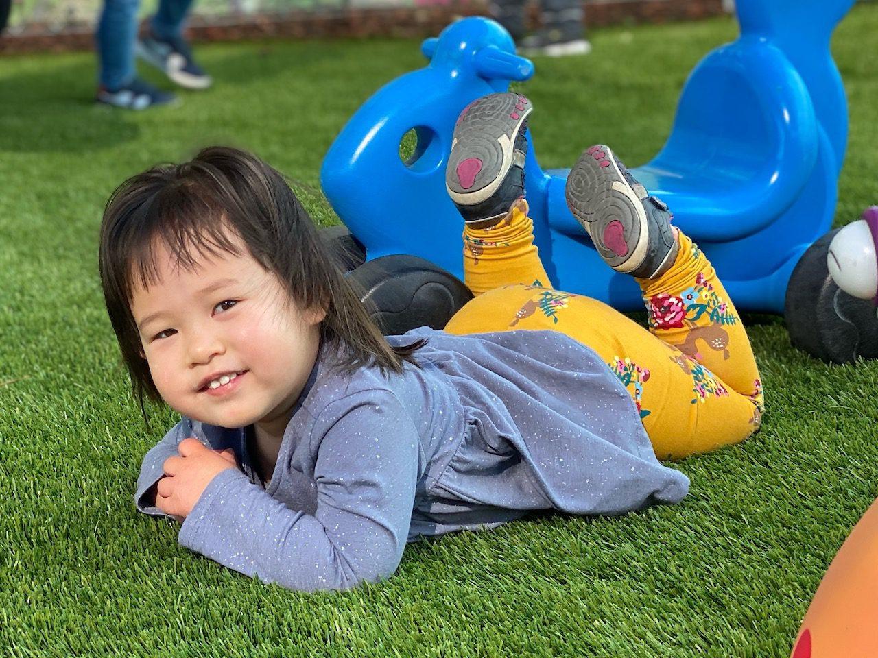 Happy Infant having fun rolling around soft turf